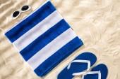 pohled na bílý modrý pruhovaný ručník, retro sluneční brýle a záklopky na písku