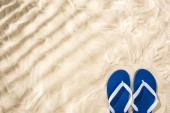 Photo top view of white blue flip flops on sand with shadows and copy space