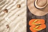 pohled na oranžovou a slaměnou čepici s černou stuhou na dřevěné desce a písku s mušle a prostorem pro kopírování