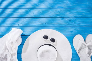 Top view of crumpled towel, white glasses, flip flops and floppy hat on blue wooden background with copy space stock vector