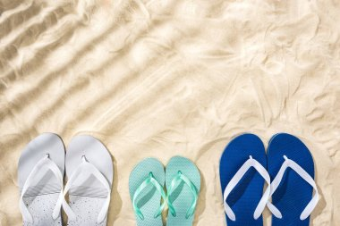 Top view of white, turquoise and white blue flip flops on sand with shadows and copy space stock vector