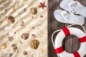 Draufsicht auf flache Lage mit weißen Flip Flops und weißem Seilrettungsring auf hölzernem braunem Brett auf geripptem Sandhintergrund mit Muscheln und Seesternen