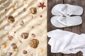 Photo top view of seashells and starfish on sand and flip flops and white towel on wooden brown board