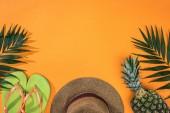 felülnézet az ananász, trópusi levelek, zöld flip papucs és barna Szalmakalapot narancssárga háttérrel és másolási hely