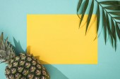 top view of pineapple, tropical leaf and yellow card with copy space on turquoise background