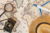 Top view of straw hat, magnifier, toy plane and film camera on world map