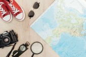 Pohled na červené gumičky, filmovou kameru, lupu, kompas, sluneční brýle a světovou mapu na dřevěné ploše