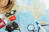 Top view of film camera, straw hat, sunglasses, gumshoes, compass, magnifier, toy car and toy plane on world map