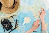 Cropped view of woman with cup of cappuccino, film camera, sunglasses and straw hat on world map