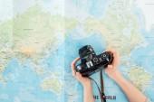 Oříznutý pohled na ženu držící filmovou kameru na mapě světa