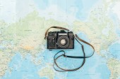 Top view of black film camera on world map