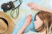 Žena s filmovou kamerou a slamákem spící na mapě světa