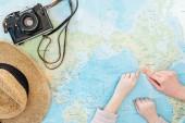 Oříznutý pohled na dítě a ženu se slamákem a filmovou kamerou ukazující prsty na mapě světa