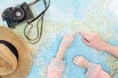 Ausgeschnittene Ansicht von Kind und Frau mit Strohhut und Filmkamera, die mit Fingern auf die Weltkarte zeigt