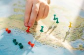 Cropped view of man with colorful push pins on world map