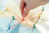 Částečný pohled na ženu s špendlíky, strunami a světovou mapou