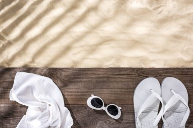 Top view of sand with copy space and white towel, retro sunglasses and flip flops on wooden brown board stock vector
