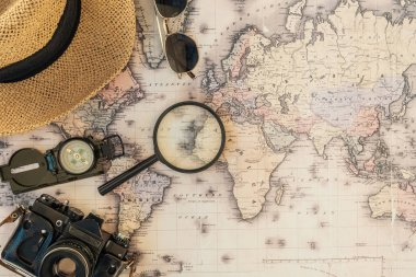 Top view of straw hat, film camera, compass, magnifier and sunglasses on world map