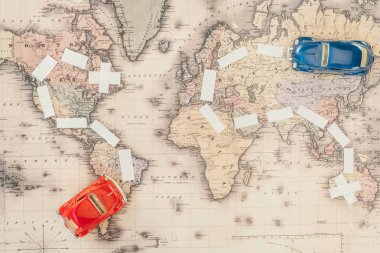 Top view of red and blue toy cars on world map