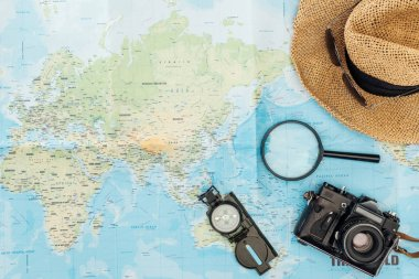 Top view of straw hat, compass, magnifier and film camera on world map stock vector