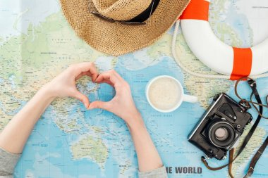 Partial view of woman with straw hat, film camera, sunglasses and lifebuoy showing heart sign on world map stock vector