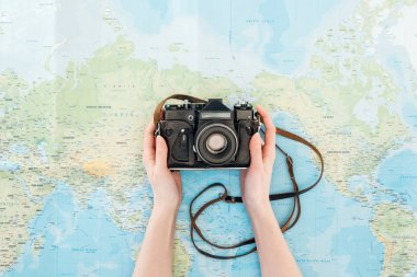 Cropped view of woman holding film camera on world map stock vector