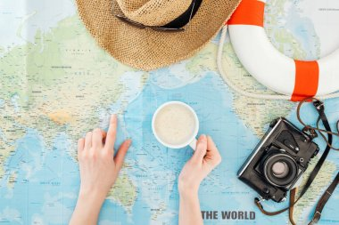 Cropped view of woman with cup of cappuccino, film camera, sunglasses and straw hat pointing with finger on world map stock vector