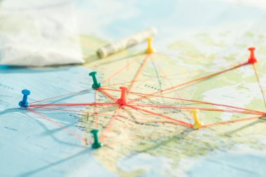 Selective focus of push pins and strings on world map