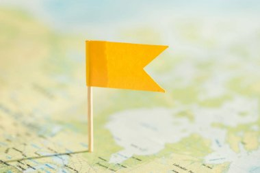 Selective focus of world map and little yellow flag stock vector