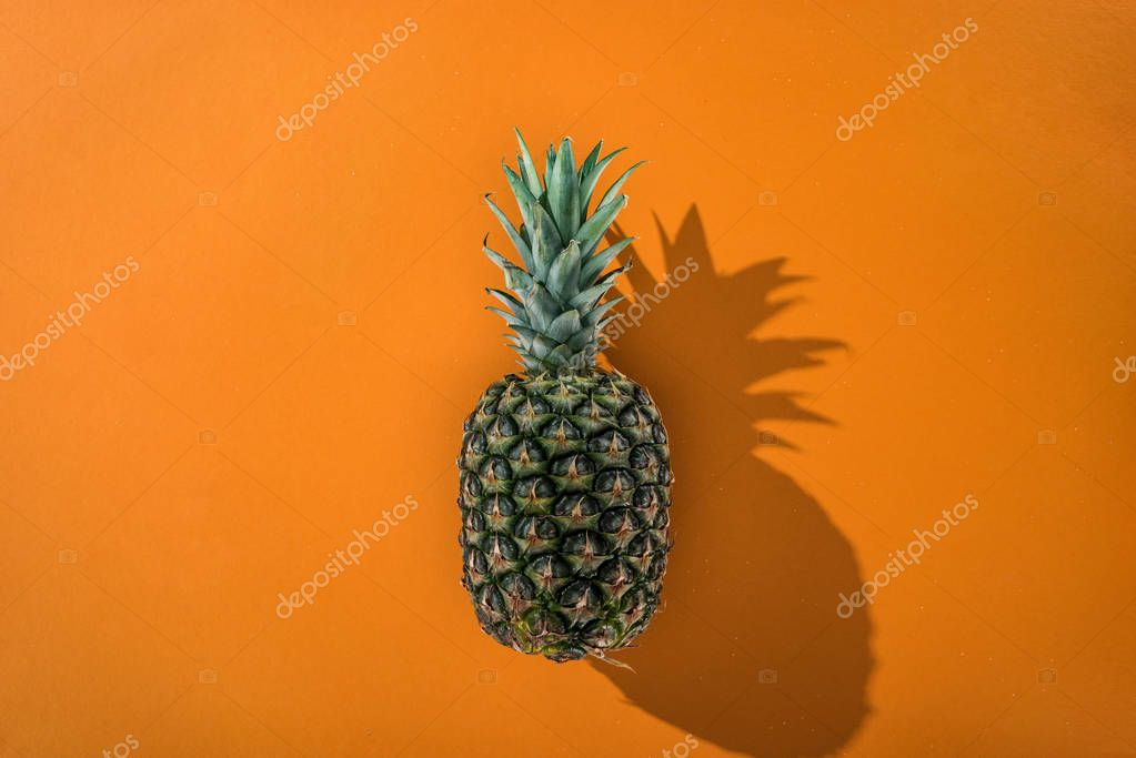 top view of pineapple with side shadow on orange background