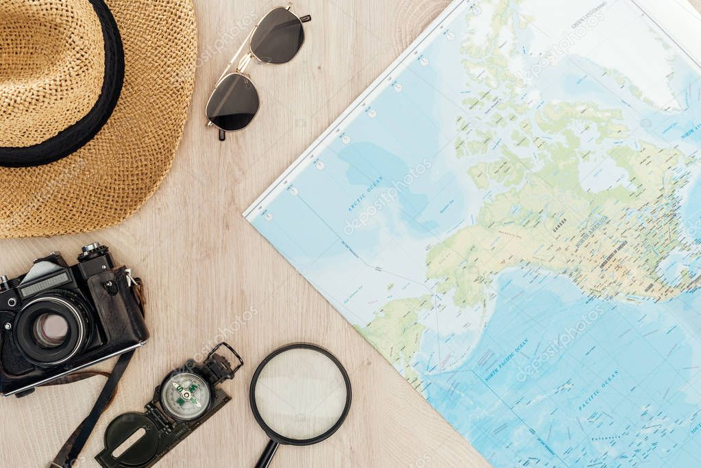 Top view of sunglasses, straw hat, compass, magnifier, film camera and world map on wooden surface stock vector