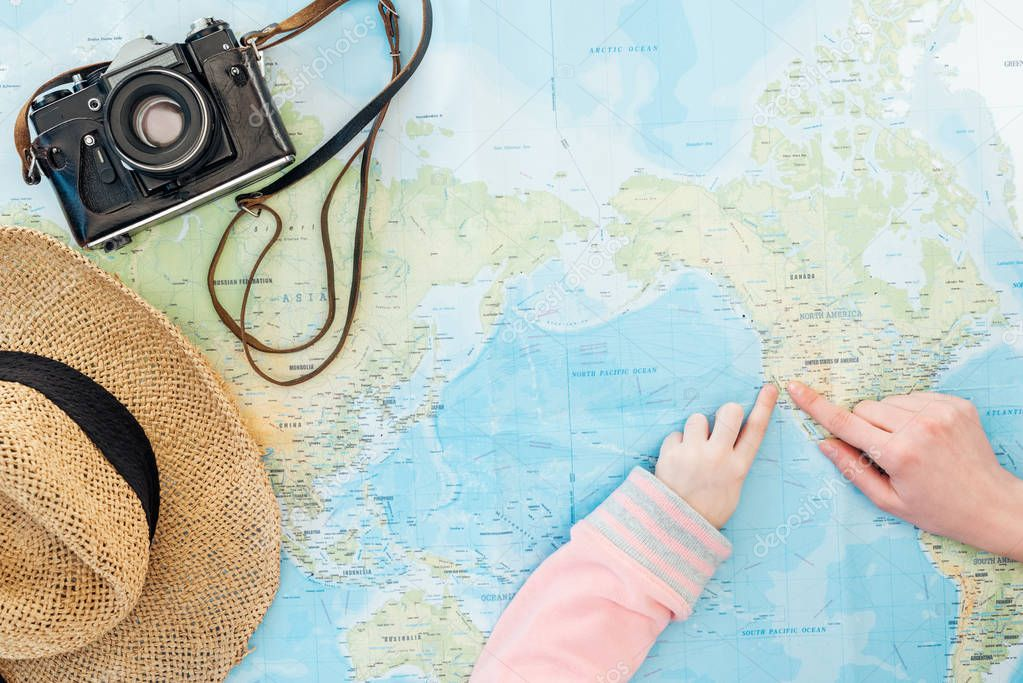 Cropped view of child and woman with film camera and straw hat pointing with fingers on world map stock vector