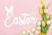 top view of painted chicken eggs and bright tulips on pink background with happy Easter lettering