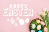 pohled na malovaná Kuřecí vejce na zelené trávě v proutavkovém koši a bílé tulipány na růžovém pozadí s bílými šťastným písmem Velikonoce