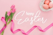top view of pink tulips bouquet with ribbon and painted eggs in wicker basket with happy Easter lettering on pink background