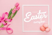 Fotografie top view of pink tulips bouquet with ribbon and painted eggs near frame with white happy Easter to everyone lettering on pink background
