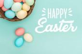 Draufsicht auf bunt bemalte Eier im Weidenkorb mit weißem fröhlichen Osteraufdruck auf blauem Hintergrund