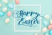 Draufsicht auf glückliche Ostern blauen Schriftzug in weißem quadratischen Rahmen in der Nähe bemalter Hühnereier auf blauem Hintergrund
