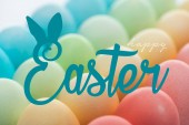 Fotografie šťastné velikonoční nápisy na pozadí barevných pomalovaných vajíček