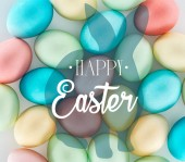 Fotografie happy Easter lettering and rabbit illustration on background of multicolored painted eggs