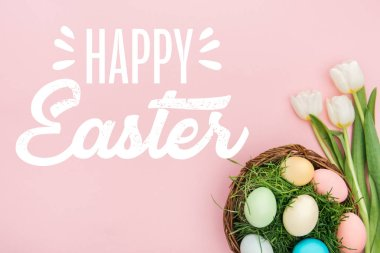 Top view of painted chicken eggs on green grass in wicker basket and white tulips on pink background with happy Easter lettering stock vector