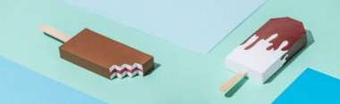 panoramic shot of handmade origami ice cream on blue and turquoise paper