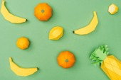 top view of handmade paper bananas, lemons and tangerines isolated on green