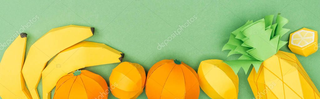 panoramic shot of multicolored handmade paper fruits isolated on green