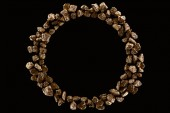 Fotografia top view of round frame made of golden stones isolated on black with copy space