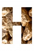 letter H made of shiny golden stones isolated on white