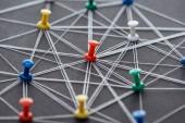 Fotografie farbenfrohe Steckstifte, die mit auf grau isolierten Saiten verbunden sind, Netzwerkkonzept