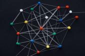 Fotografie Draufsicht auf Push-Pins, die mit auf Schwarz isolierten Saiten verbunden sind, Netzwerkkonzept