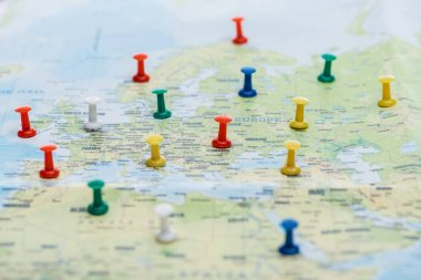 selective focus of colorful push pins on world map