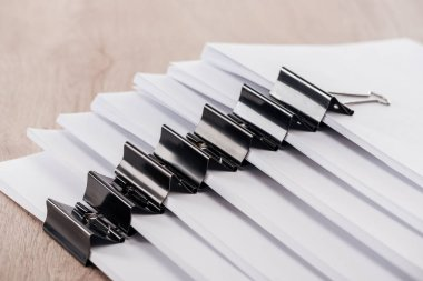 arranged stacks of blank paper with metal binder clips on table